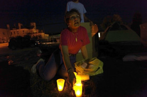Marianne Kernan turns candle lights on for sleep-in participants to light the way